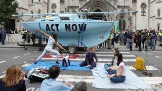 Extinction Rebellion climate activists practice yoga during a protest outside the Royal Courts of Justice in London