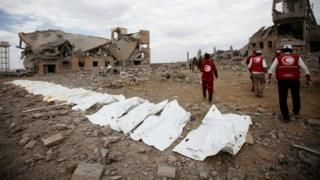 Red Crescent medics walk next to bags containing the bodies of victims of Saudi-led airstrikes on a Houthi detention centre in Dhamar, Yemen,