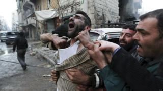 A father reacts after the death of two of his children by shellfire in the rebel-held al-Ansari area of Aleppo, Syria (3 January 2013)