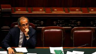 Italian Economy Minister Giovanni Tria, pictured alone, muses in Italy's dark oak and red leather parliament chamber