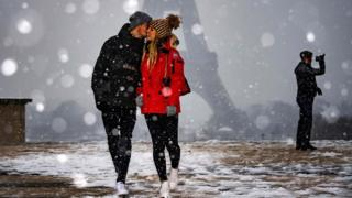 A couple is pictured in front of the Eiffel Tower as snow falls over Paris on 22 January 2019