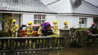 A group of firefighters helping a woman from her home