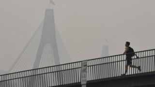 A man runs over a bridge during a smoky haze in Sydney on Tuesday