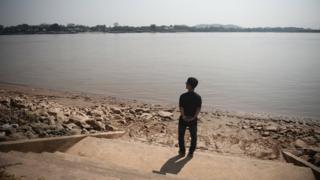คิม ฮัก มินยืนอยู่ริมแม่น้ำโขง ใกล้กับบริเวณที่เขาขึ้นเรือเหยียบเมืองไทยเป็นครั้งแรก