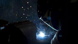 An engineer welding metal