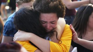Ellie Branson is comforted as she joins with others after a school shooting that killed 17 to protest against guns on the steps of the Broward County Federal courthouse on February 17, 2018 in Fort Lauderdale, Florida