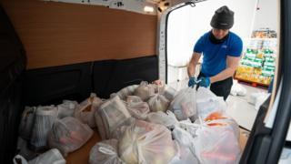 Volunteers help load a delivery van