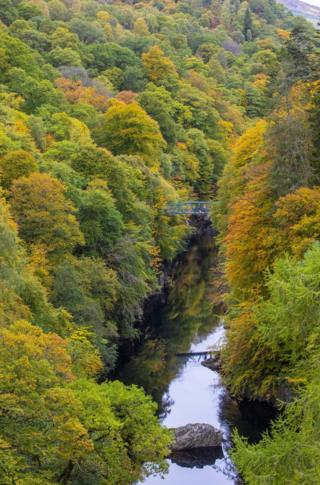 Warna-warna hijau, merah dan kuning terpantul dari pepohonan di sisi jembatan River Barry dekat desa Killiecrankie in Perthshire
