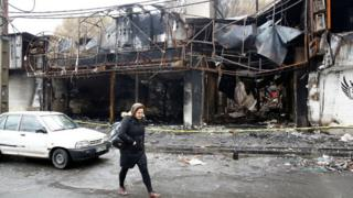 An Iranian woman walks past a shopping centre that was burned during protests over increasing fuel prices in the city of Shahriar, Alborz province, Iran, 20 November 2019.