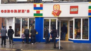 People gather outside Osborne's toy shop in Rusden to see its frontage covered in Lego.