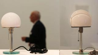 Lâmpada original de design icônico feita por Wilhelm Wagenfeld ao lado de uma réplica moderna