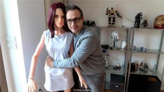 圖中,桑托斯(Sergi Santos)手抱自己的一項發明,這是一個他認為能幫助挽救婚姻的性愛機器人。(Credit: Getty Images)
