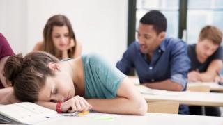 Uma jovem estudante adormecida sobre os livros