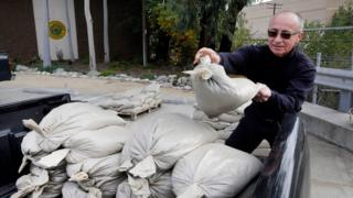 A man piles sandbags into his truck