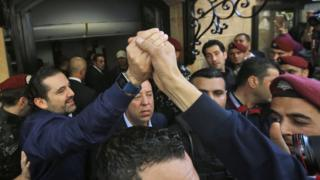 Lebanese prime minister Saad Hariri (L) greets his supporters upon his arrival at his home in Beirut