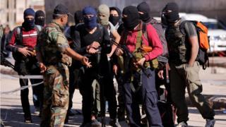 Humus'taki muhalifler, tahliye sırasında ellerinde silahlarla bir Suriye ordusu mensubuyla konuşurken