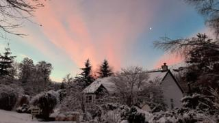 A snow covered house under pink skies