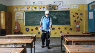 A Palestinian worker wearing a protective face mask sanitizes a United Nations-run school in Gaza City, Gaza - 5 August 2020