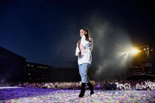 Ariana Grande wipes away a tear while on stage.