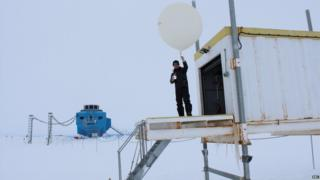 Peter Gibbs standing outside a small shed, holding a large white balloon in his hand. Halley research base lies in the background. Around is pure white snow and the sky is white