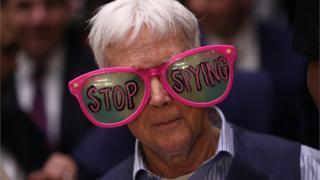 """Čovek na svedočenju Zakerberga pred Senatom nosi velike naočare na kojima piše """"Prestanite sa špijuniranjem"""""""