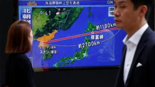 Füze haberini televizyon ekranlarından izleyen Japonlar