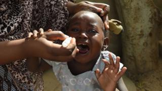 Сотрудник ЮНИСЕФ пытается привить ребенка