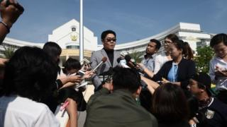 Kong Suriyamontol (C-with sunglasses), the Thai lawyer for Japanese national Mitsutoki Shigeta, speaks to the press after his client was granted paternity rights to his children, at a juvenile court in Bangkok on February 20, 2018.