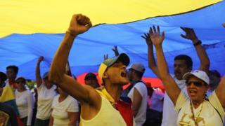 Manifestante embaixo da bandeira da Venezuela