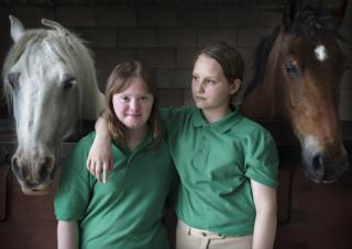 Portrait of sisters Hattie & Charlotte stood with horses from the on-going project, Our Human Condition, by Paul Wenham-Clarke in 2017.