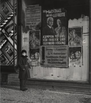 "Vishniac's daughter Mara posing in front of an election poster for Hindenburg and Hitler that reads ""The Marshal and the Corporal: Fight with Us for Peace and Equal Rights"". Wilmersdorf, Berlin, 1933."