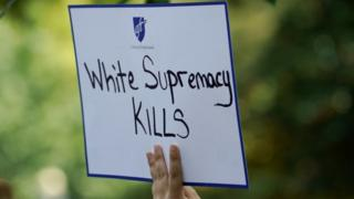 A woman holds a sign during a rally against guns and white supremacy in the wake of mass shootings in Dayton and El Paso
