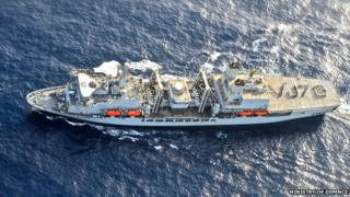 RFA and Royal Navy personnel spell out the message VJ70 on the deck of Royal Fleet Auxiliary ship Fort Victoria