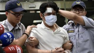 عناصر من الشرطة التايوانية تحتجز المهاجم