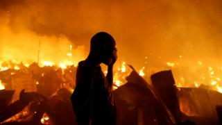 A resident of Kenyan slum attempts to extinguish a fire that broke out in the at the Kijiji slums in the Lang'ata area of the capital, Nairobi - 28 January 2018