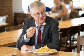 First Minister Mark Drakeford tucked into chips on a visit to a reopened restaurant in Cwmbran