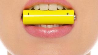 Una mujer con una batería en la boca