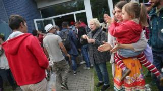 Migrants who had arrived on a train hours earlier arrive to locals welcoming them with soap bubbles and balloons at the Jahn-Sporthalle gymnasium in Neukoelln district on 8 September 8 2015 in Berlin