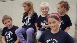 Children from the litter picking group sit on a wall