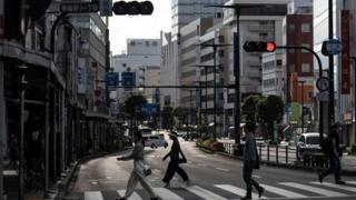 People cross a road in Japan where the nationwide state of emergency has been lifted for 39 of the country's 47 prefectures.