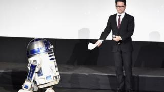 R2-D2 (L) and director J.J. Abrams speak onstage the World Premiere