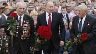 El presidente ruso Vladimir Putin (en el centro) flanqueado por dos veteranos de guerra en un acto de homenaje el 12 de julio de 2013
