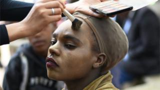 A woman gets her make-up done during the Valentine Street Family Bash in Nairobi on 14 February 2020.