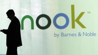 man standing outside Nook advert