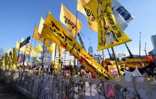 Protesters hold yellow flags during a rally urging the impeachment of South Korea's President Park Geun-Hye outside the National Assembly in Seoul on December 9, 2016