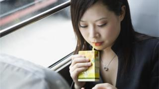 A woman sips from a drink carton with a plastic straw