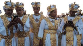 Traditionally attired Ethiopian Orthodox Christians use smart phones - Friday 18 January 2019