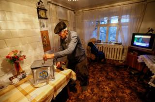 A local resident casts his ballot into a portable ballot box at his house during a presidential election in the village of Suruceni, outside Chisinau, Moldova