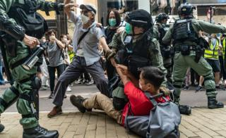 Pro-democracy supporters scuffle with riot police during a rally