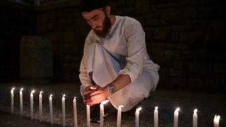 A well-wisher helps to light 49 candles as he pays respects to victims outside the hospital in Christchurch on March 16, 2019